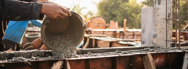 Pracownik wylewa cement do budowy domu na placu budowy
