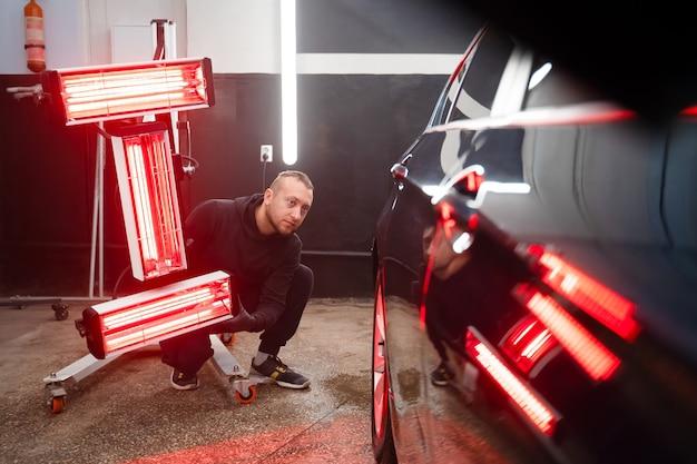 Pracownik wyszczególniający szczegóły z lampami podczerwieni w pobliżu samochodu.