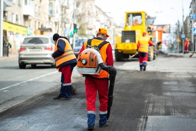 Pracownik z dmuchawą do liści, usuwający kurz dla lepszej przyczepności asfaltu podczas prac remontowych torów tramwajowych