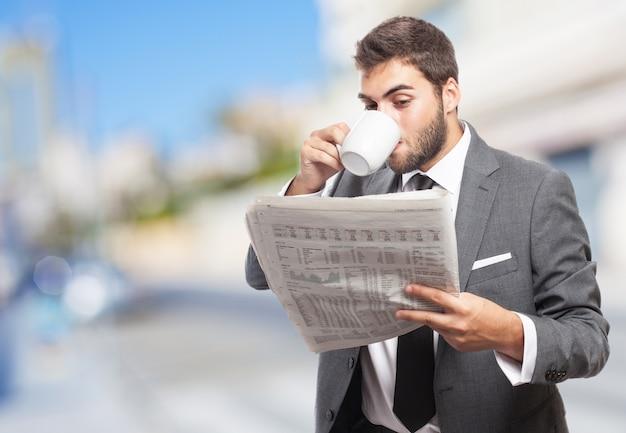 Pracownik z filiżanka kawy czytania wiadomości