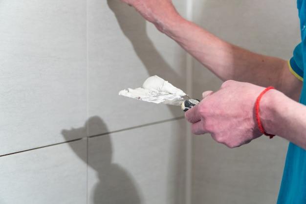 Pracownik z gumową szpatułką wypełnia szwy roztworem technologia układania płytek