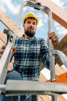 Pracownik z kaskiem przy użyciu drabiny do budowy dachu domu