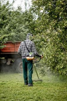 Pracownik z kosiarką gazową w rękach, koszący trawę przed domem
