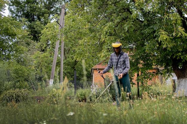 Pracownik z kosiarką gazową w rękach, koszący trawę przed domem.