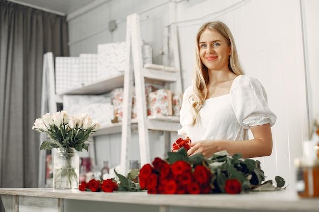 Pracownik z kwiatami. kobieta sprawia, że bukiet. ładna dziewczyna pracuje