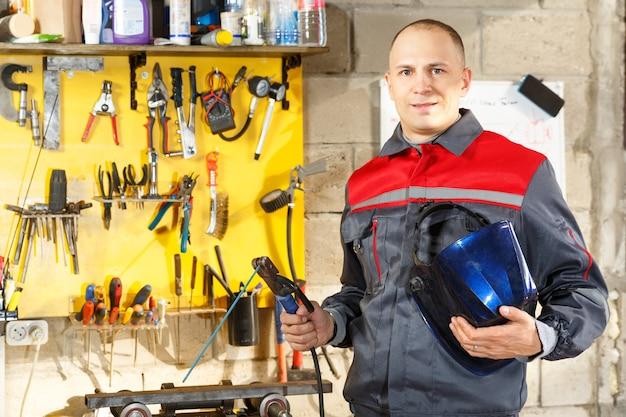Pracownik z maską ochronną do spawania metalu w domu budowlanym