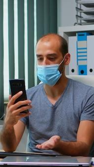 Pracownik z maską ochronną rozmawia przez kamerę internetową z liderem firmy siedzącym w nowoczesnym biurze. freelancer pracujący w nowym normalnym miejscu pracy na czacie prowadzący wirtualną konferencję, spotkanie przez internet