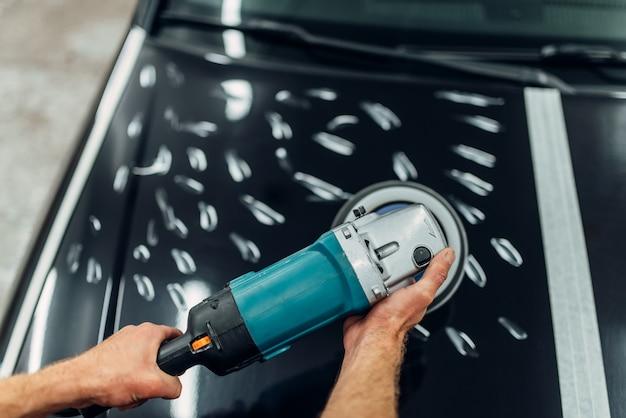 Pracownik z maszyną do polerowania czyści maskę samochodu