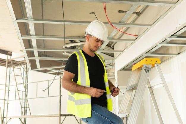 Pracownik z miarką na budowie