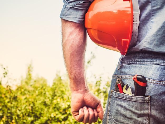 Pracownik z narzędziami i pomarańczowym hełmem