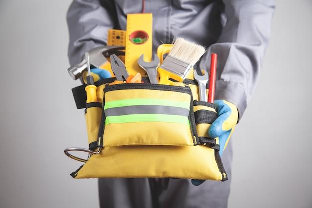 Pracownik z paskiem narzędzi. narzędzia budowlane