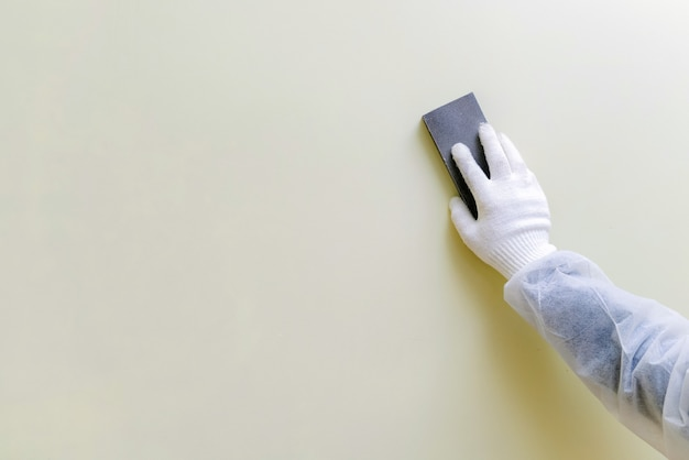 Pracownik z rękawicami i ochronną odzieżą roboczą, szlifujący ścianę.