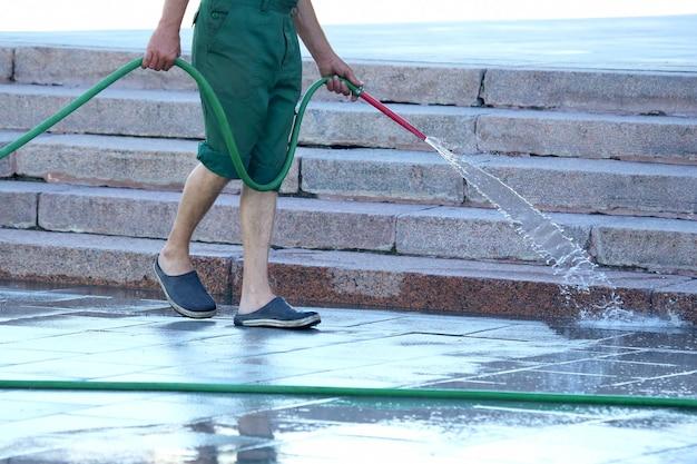 Pracownik z węża podlewającego ulicę miasta