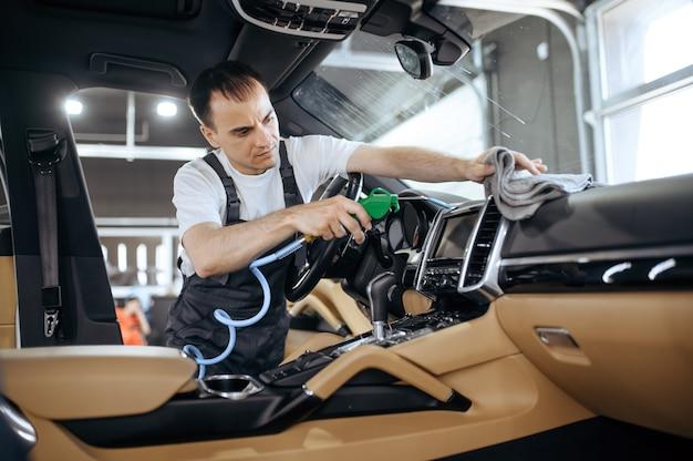 Pracownik z wiatrówką czyści kratki samochodowe, pranie chemiczne i detale