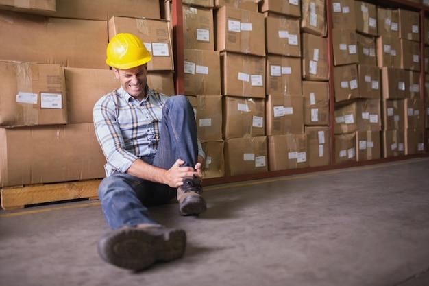 Pracownik z zwichniętą kostką na podłoga w magazynie