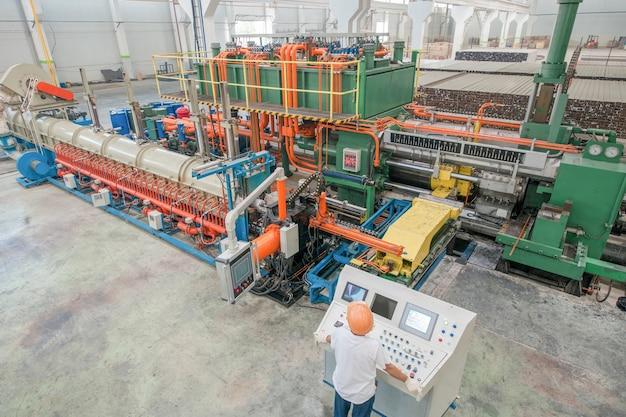 Pracownik za deską rozdzielczą w warsztacie do produkcji profili aluminiowych
