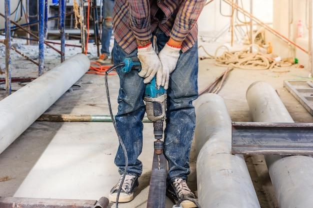 Pracownik za pomocą elektrycznego śrubokręta do mocowania konstrukcji stalowych