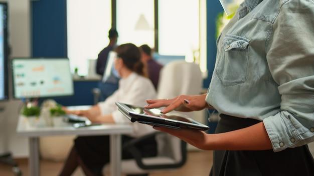 Pracownik za pomocą tabletu stojący w pokoju biurowym, podczas gdy zespół analityków finansowych pracuje w tle. wieloetniczni współpracownicy szanujący dystans społeczny w firmie podczas pandemii koronawirusa.
