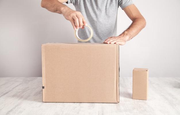 Pracownik za pomocą taśmy uszczelniającej karton. produkty, handel, sprzedaż detaliczna, dostawa