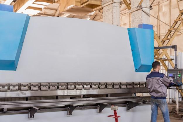 Pracownik za pulpitem sterowniczym, maszyna do formowania prasy typu zamkniętego