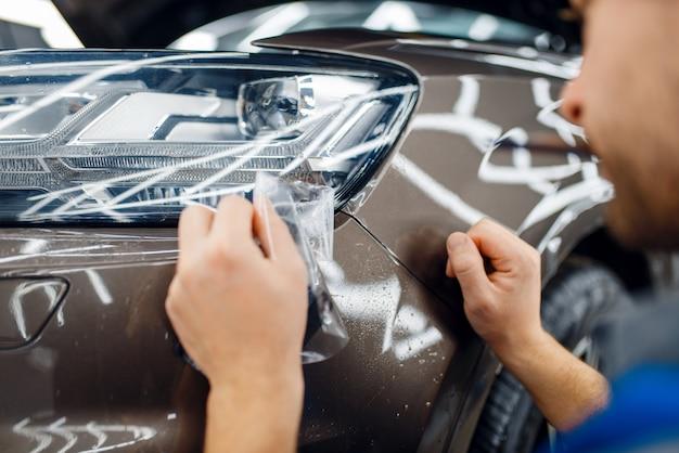 Pracownik zakłada folię ochronną na maskę samochodu