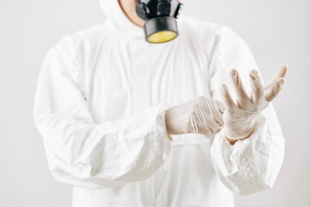 Pracownik zakładający kombinezon i rękawice ochronne