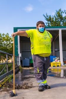 Pracownik zakładu recyklingu lub czystego punktu i śmieci z maską na twarz i zabezpieczeniami, covid-19. portret pracownika z miotłą