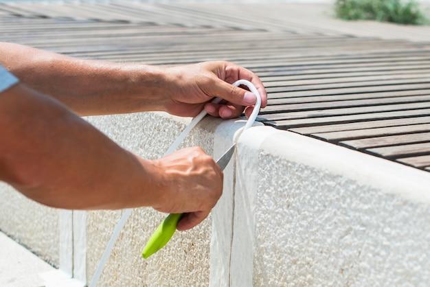Pracownik zamyka szczelinę między betonowymi płytkami ulicy. za pomocą białej taśmy i noża. naprawa domu. praca na zewnątrz. robi to sam
