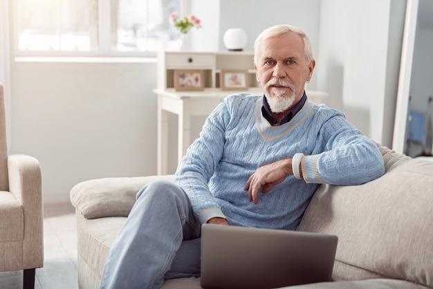 Pracownik zdalny. przystojny starszy mężczyzna pozuje siedząc na kanapie i przy użyciu swojego laptopa, pracując nad nim