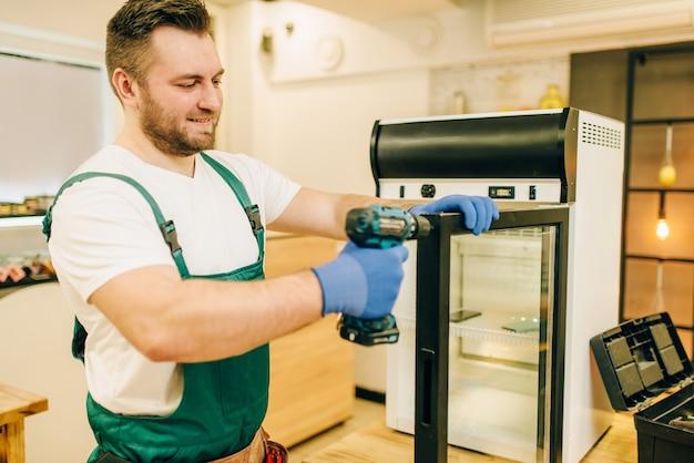 Pracownik ze śrubokrętem naprawia drzwi lodówki