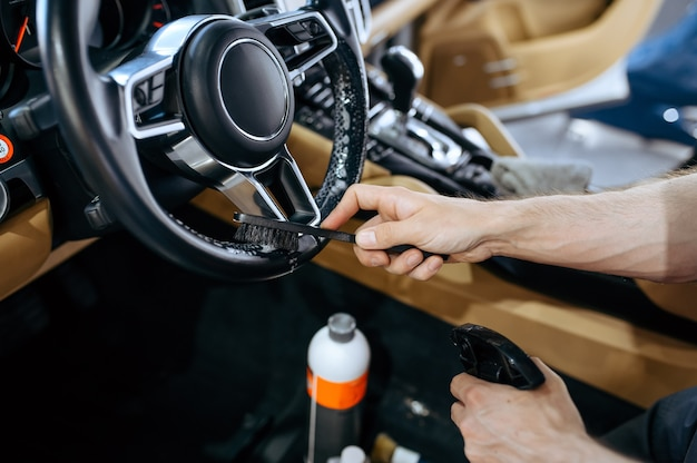 Pracownik ze szczotką wyciera kierownicę samochodu, czyści chemicznie i detaluje