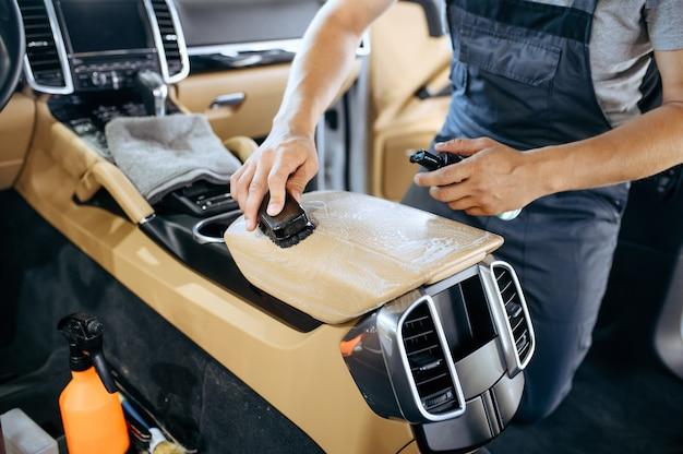 Pracownik ze szczotką wyciera podłokietnik samochodowy, czyści chemicznie i detalicznie