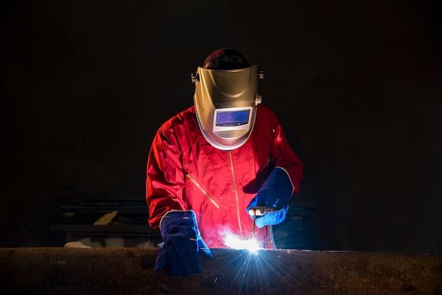 Pracownik zgrzewa część stali w warsztacie budowlanym