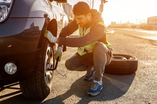 Pracownik zmienia zepsute koło samochodu. kierowca powinien wymienić stare koło na koło zapasowe. mężczyzna odmieniania koło po awarii samochodu. transport, koncepcja podróży