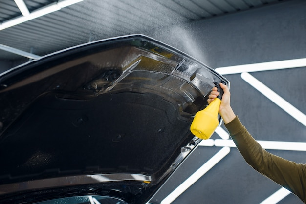 Pracownik zwilża powierzchnię maski samochodu sprayem przed nałożeniem folii ochronnej. montaż powłoki chroniącej lakier samochodu przed zarysowaniami. nowy pojazd w garażu, procedura tuningu
