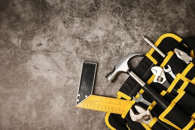 Pracownika budowlanego pasek z narzędziami na betonowym tekstury tle. wolne miejsce na tekst