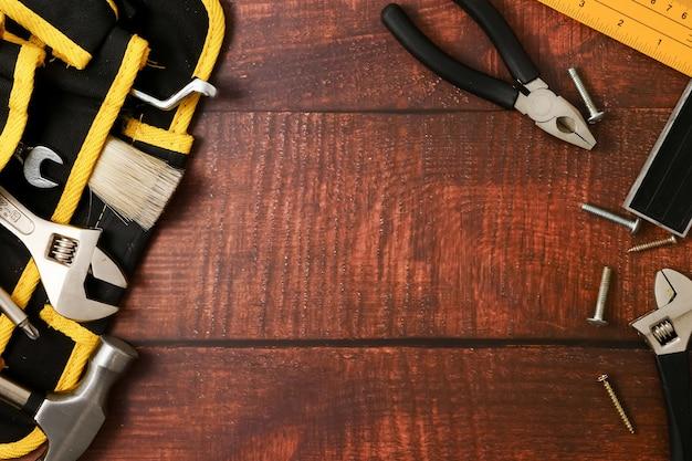 Pracownika budowlanego pasek z narzędziami na drewnianym stołowym tle. wolne miejsce na tekst