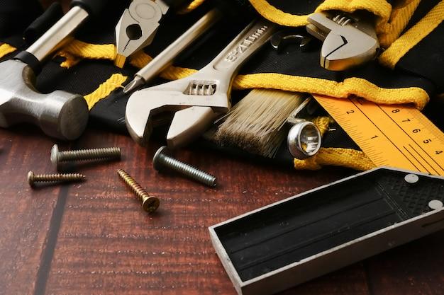 Pracownika budowlanego pasek z narzędziami na drewnianym stołowym tle.