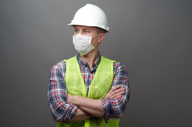 Pracownika mężczyzna jest ubranym higieniczną maskę i ochronnego ciężkiego kapelusz.