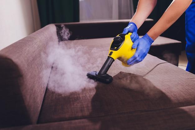 Pracownika pralni chemicznej usuwa brud z meble w mieszkaniu, zbliżenie.