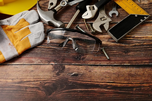 Pracowników budowlanych narzędzia na drewnianym stołowym tle. wolne miejsce na tekst
