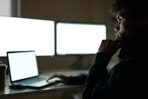 Pracuj całą noc, skoncentrowany młody chłopak siedzący w ciemnym pokoju przed wieloma monitorami komputerowymi, podczas gdy