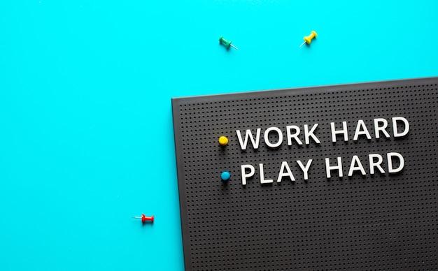 Pracuj ciężko baw się dobrze z tekstem na kolorowym stole na biurku