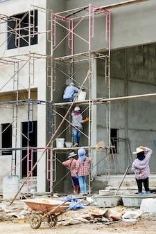 Pracuj na wysokości, pracownicy budowlani są otynkowani na rusztowaniach na placu budowy.