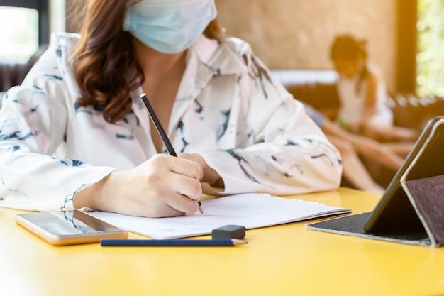 Pracuj w domu. kobieta w kwarantannie dla koronawirusa covid-19, ubrana w maskę ochronną do pisania na notebookach pracujących w domu, podczas gdy jej dzieci bawią się w domu podczas wybuchu koronawirusa