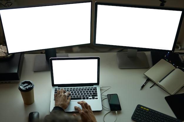 Pracuj w dowolnym momencie pod kątem widzenia rąk mężczyzny siedzącego przy stole przed wieloma komputerami