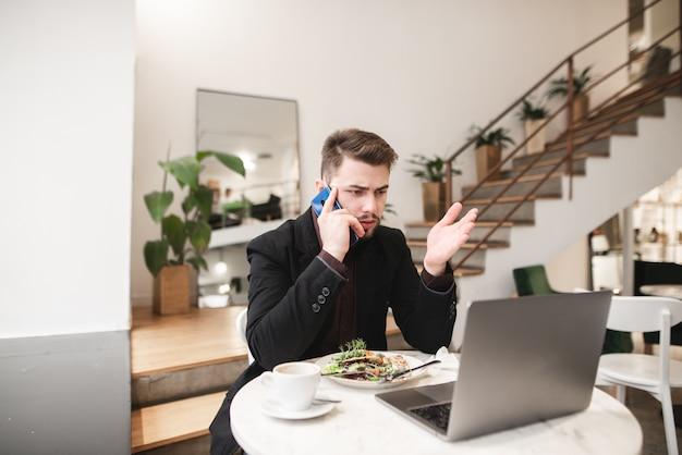 Pracuj w kawiarni na lunch. biznes człowiek pije kawę i zjada sałatkę.
