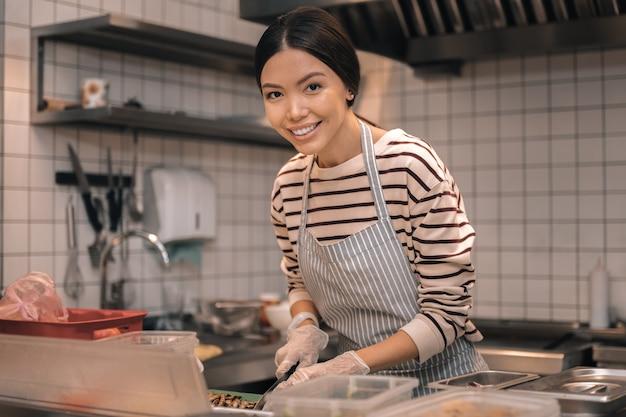 Pracuj w kuchni. piękna ciemnowłosa odnosząca sukcesy właścicielka kafeterii pracująca w kuchni