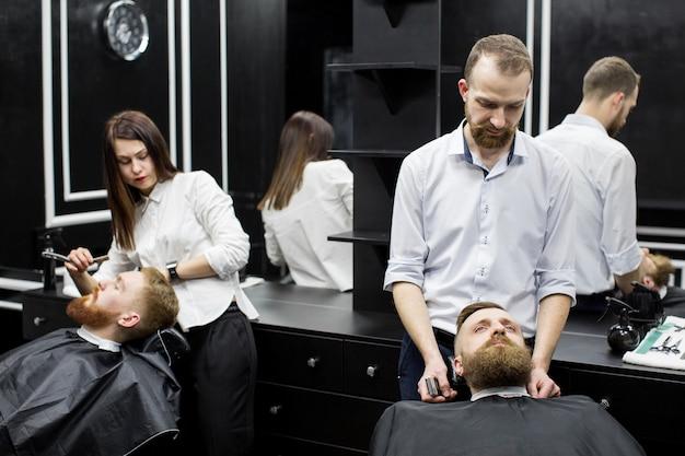 Pracuj w zakładzie fryzjerskim. dwóch mistrzów w pracy.