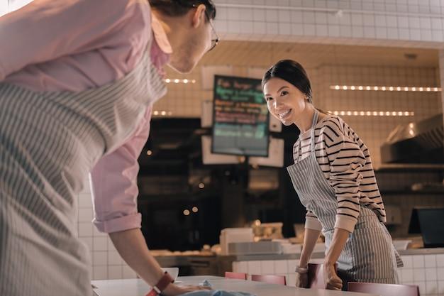 Pracuj z chłopakiem. piękna wesoła ciemnowłosa kelnerka pracująca ze swoim przystojnym, opiekuńczym chłopakiem